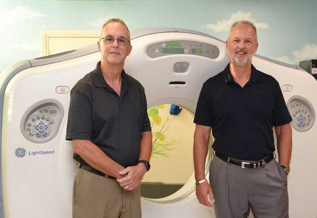 Chambliss brothers standing in front of scanning machine